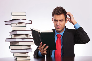 confused man reading at desk