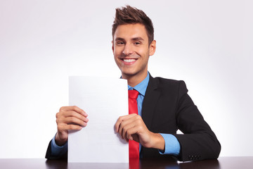 man at desk showing some papers