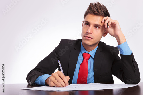 man at desk thinking what to write