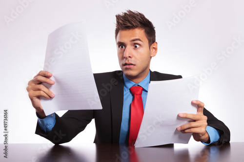 surprised man reads letter at desk