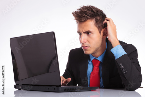 confused man looks at laptop