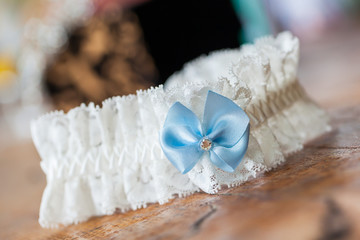A white linen garter with a blue bow.