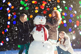 Three girls building a snowman