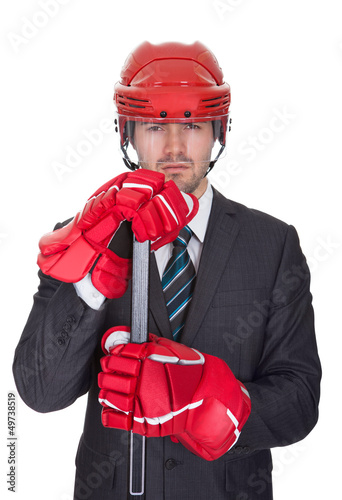 Competitive businessman wearing hockey equipment