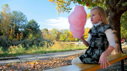 Child eating cotton candy in the park