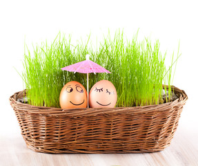 two Funny smiling  eggs under umbrella  in  basket with grass