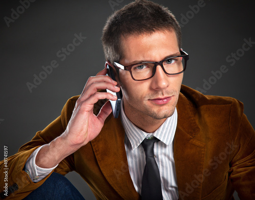 Young interesting businessman talking on phone