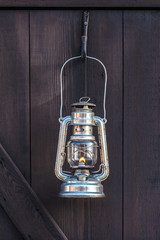 Old fashioned lantern on a brown wooden wall