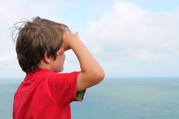 Young boy aged 7 looking out to sea