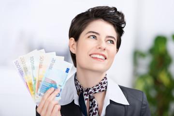 glückliche frau hält geldscheine in der hand