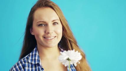 beautiful woman sniffing white chrysanthemum and smiling