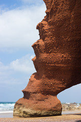 huge red cliffs with arch on the beach Legzira. Morocco