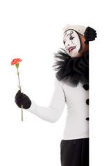 Männlicher Clown mit Blume blickt ums Eck