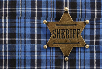 Sheriff star badge attached on blue plaid cowboy shirt