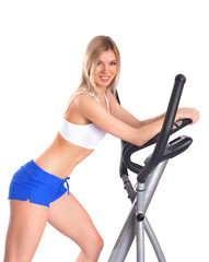 Slim woman leans on gym equipment