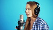 woman singing with headphones at studio
