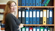 Woman standing behind bookshelves with file folders and smiling