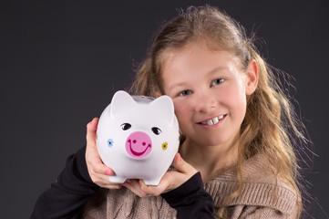 Mädchen zeigt stolz ihr Sparschwein