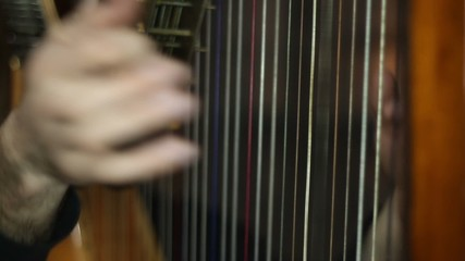 Male hands playing the harp