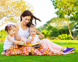 Fototapety Woman with daughter and son read fairytale