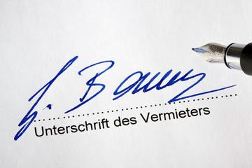 Unterschreiben eines Mietvertrags durch den Vermi