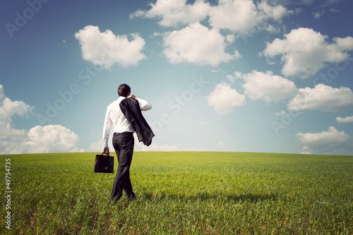 businessman in a suit walking on a spacious green field with a b
