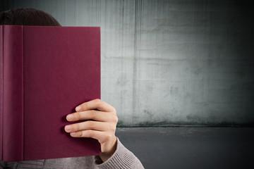 joven leyendo con pared de fondo