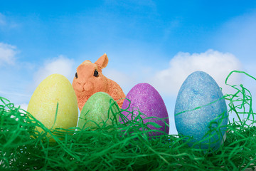 Bunt bemalte Eier mit Osterhase auf einer Wiese