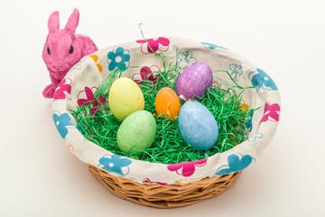 Hase am Osterkorb mit bunten Eiern