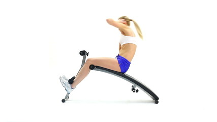 Sporty blonde exercising muscles on bench