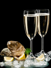 Two champagne glasses and oysters shells on black background