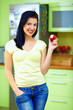 smiling woman eating apple, kitchen interior