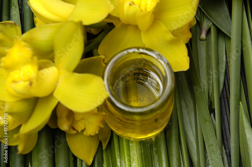 oil bottles and yellow orchid on bamboo grove
