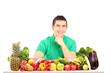 Young man posing with a pile of fruits and vegetables