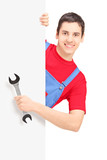 Repairman holding a wrench and posing behind a blank panel