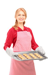 Mature woman holding a tray with baked cookies