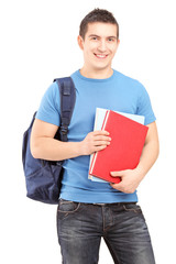 Smiling male student with backpack holding books