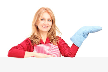 Smiling woman in apron posing with a cooking mitten behind a pan