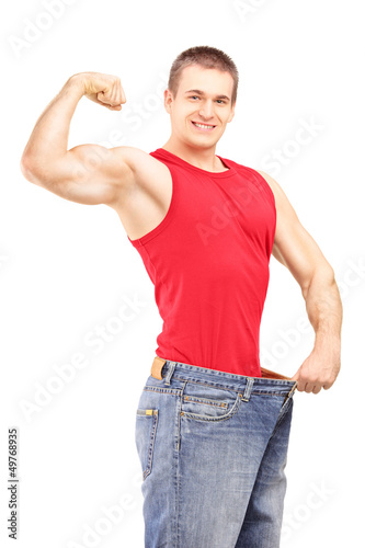 Weight loss man in an old pair of jeans showing his muscular bod