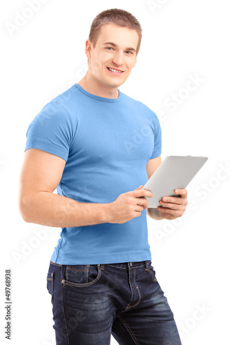 Young man holding a tablet and looking at camera