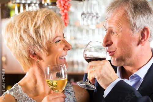 Starsza para przy barem z szkłem wino w ręce