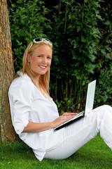 Frau mit Laptop Computer im Garten