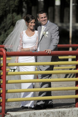 bride and groom are lean on the fence of the bridge in the town
