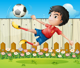 A boy playing soccer inside the fence