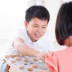 Asian children playing Chinese chess
