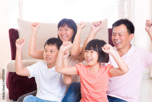 Asian family playing game at home.