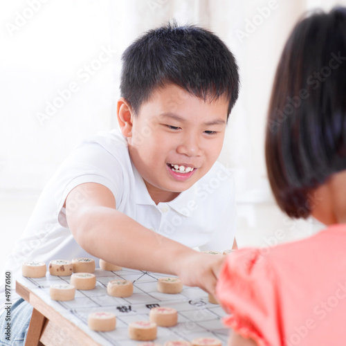 Asian children playing Chinese chess