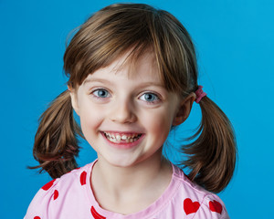 happy little girl portrait and blue background