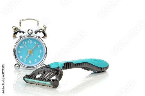 A disposable razor next to a mini alarm clock. Morning routine