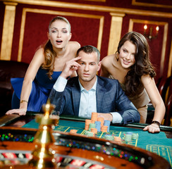 Man with two women playing roulette at the casino